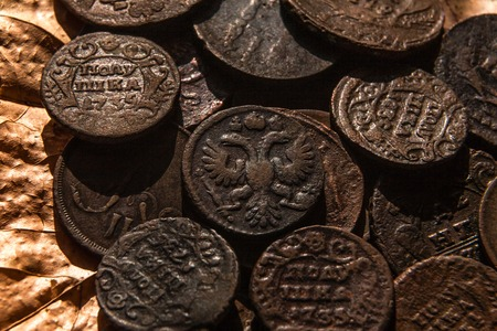 oxides: ancient copper coins of a half-ear of the eighteenth century in strong oxides against the background of dry leaves Stock Photo