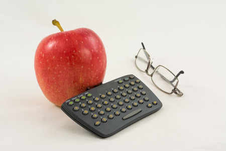 Red apple with a mini keyboard and glasses on a white background  Fun business still life  photo