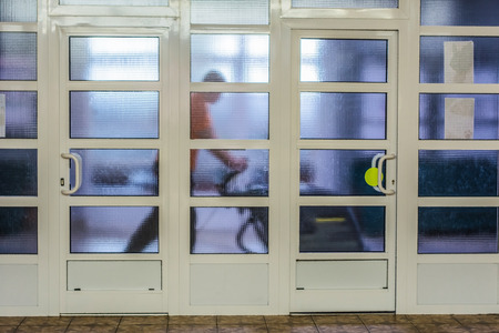 glass partition: The man behind a glass partition rubs floor