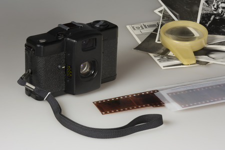 compact camera: Old compact camera negatives blackandwhite photos and a magnifying glass on a table on a white background Stock Photo