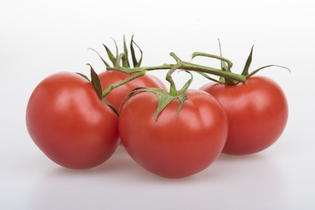 four objects: Four red tomatoes with green twig on a table on a white background
