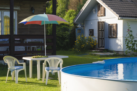 Plastic Table, Chairs And Sun Umbrella Next To The Summer Swimming Pool.  Stock Photo