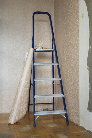 Folding staircase and roll of wallpaper before sticking in the room