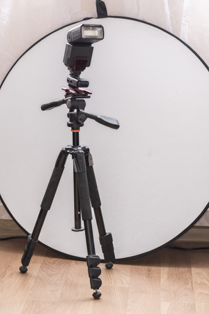 Flash on a tripod and a round white reflector are accessories for photographing a portrait. Фото со стока