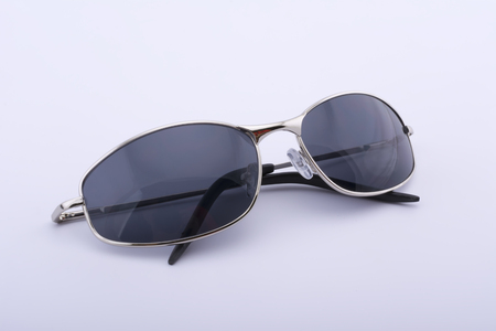 Gray sunglasses with a gold rim on a white background Imagens