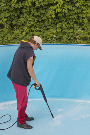 A woman cleaning a summer pool with a high pressure washer Imagens