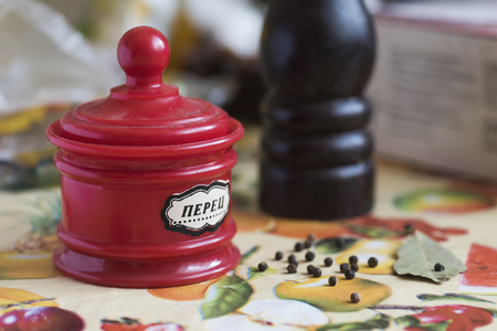 Red pepper tank, pepper mill, bay leaf and black pepper peas on the kitchen table Imagens