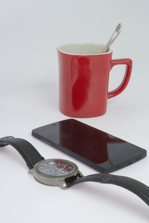 Watch, smartphone and red cup on a white table