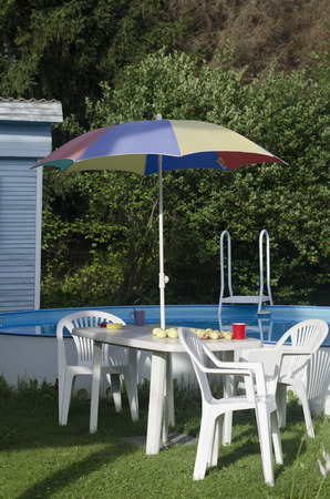Plastic table, chairs and sun umbrella next to the summer swimming pool.