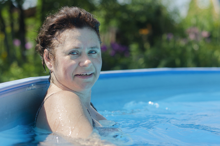 Woman at the side of a summer swimming pool on a bright sunny day Imagens