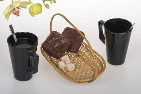 Black coffee cup, chocolate muffins and yellow orchid on a white background - Still Life Imagens
