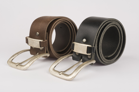 Two mens leather belt, black and brown on a table on a white background