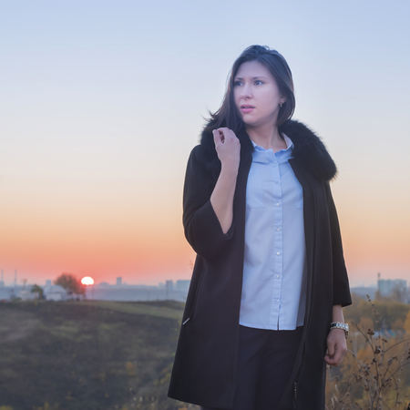 Young woman in blue blouse and black coat at sunset in autumn Imagens