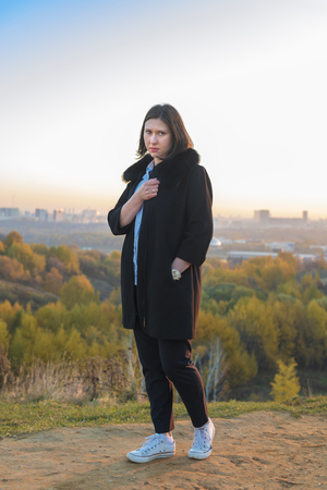 Young woman in a blue blouse and a black coat for a walk in the autumn park
