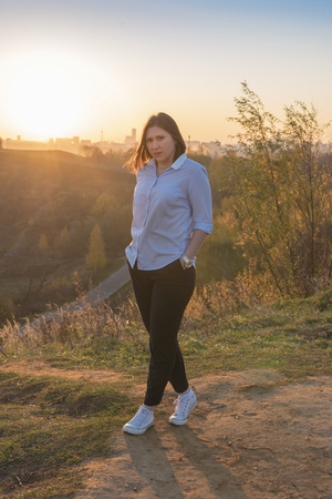 Young woman in blue blouse and black pants at sunrise in autumn