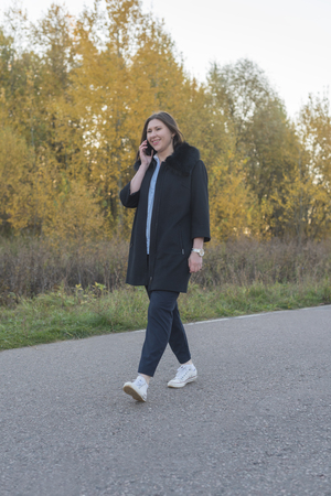 Young woman in a blue blouse and black coat talking on a mobile phone in the autumn park Imagens