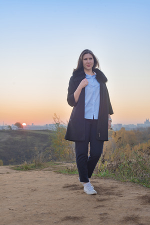 Young woman in blue blouse and black coat at sunrise in autumn