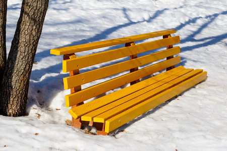 Yellow bench in the park in the snow