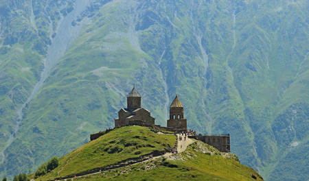Church of the Holy Trinity on the background of the Caucasus Mountains Stock Photo