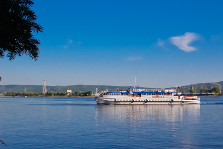 A small boat sails along the river against the backdrop of the mountains and the blue sky Stock Photo