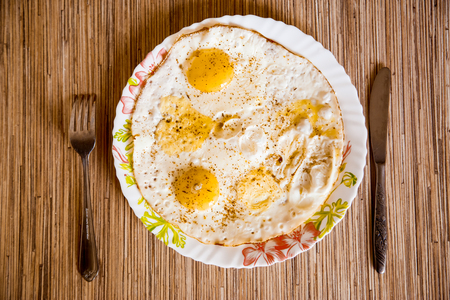 Fried eggs lie on a plate on a wooden table