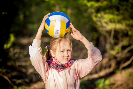 The girl with the ball is in the woods in the spring
