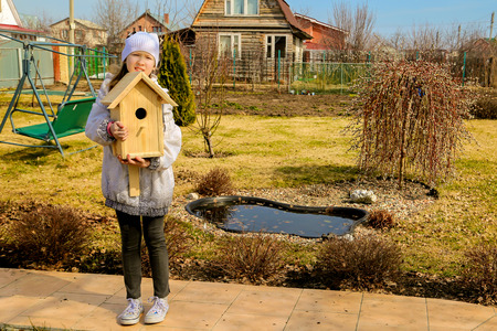 educacion ambiental: The girl is holding a birdhouse for birds in the spring