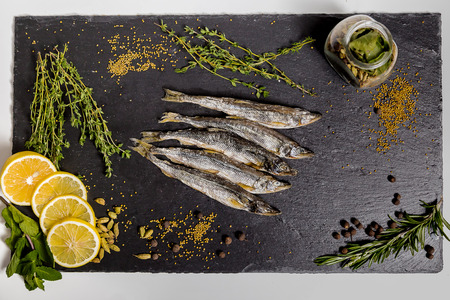 dried smelt lies on a black dish Stock Photo
