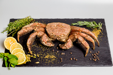 crab bristly hairy lie on a black dish