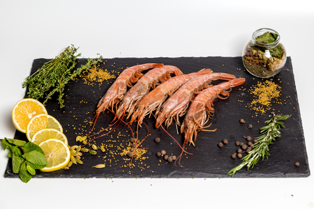 shrimp langoustine lie on a black plate