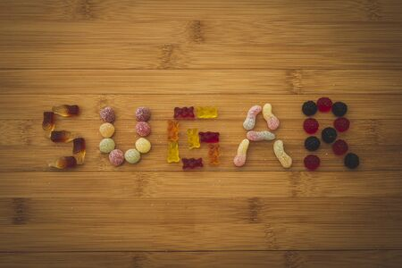 The word sugar spelled on a wooden plank with different kinds of colorful pieces of candy. The sweets are placed on a wooden plank with sugar sprinkled around them.