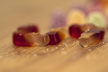 A portrait of different pieces of colorful candy lying on a wooden table with sugar sprinkled all around them. The sweets in focus are shaped like cola bottles.