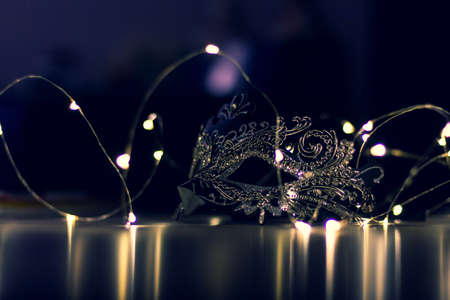 A scenic portrait of a mask lying on a table surrounded by fairy lights. The dark moody evening light casts some mystery over the mask.