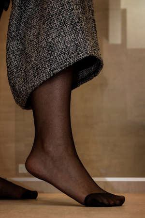 A close up portrait of a foot in black pantyhose of a girl pulling up her skirt. The nylon is reinforced at the toes.