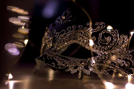 A portrait of a mysterious mask on a wooden table surrounded by lights. It is perfect to hide someones identity on a venetian masked ball.
