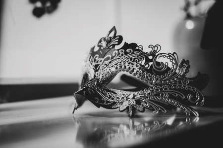 A black and white portrait of a mysterious venetian mask lit by a window. A great way to hide your identity on a masked ball, carnival or halloween party.