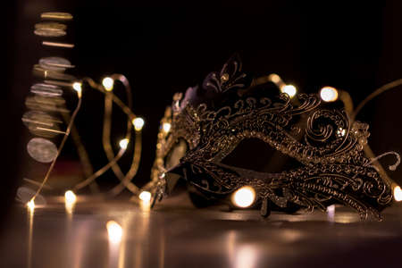 A portrait of a venetian mask on a wooden table surrounded by fairy lights. The mask is to be worn to hide someones identity on a masked ball.