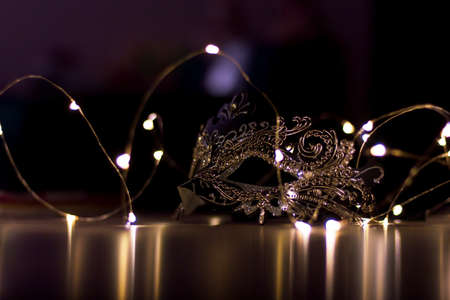 A scenic portrait of a mask lying on a table surrounded by fairy lights. The dark environment casts some mystery over the mask.