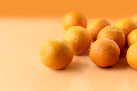 A portrait of multiple fresh oranges filled with vitamin c. The healthy pieces of fruit are displayed on an orange background.