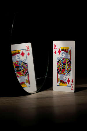 Brecht, Belgium - 29 May 2020: The diamond king of a deck of playing cards looking at its own reflection in the mirror. Normally it looks like pride and powerful picture, but here it becomes sadness. Foto de archivo