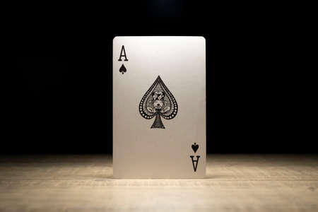 Brecht, Belgium - 29 May 2020: A portrait of the ace of spades standing up in the spotlight on a wooden table surrounded in darkness. There are no other playing cards of the deck in the picture.