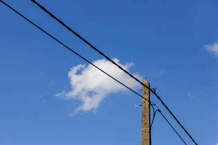 A portrait of an electric pole with electric wires in a blue sky with a few white clouds. The high voltage powerlines is going both ways starting from the pole.