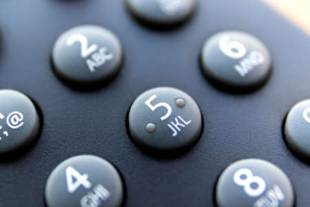 A close up portrait of the numeric buttons of a television remote control. The button with number 5 is in the center, surounded by the others of its kind to use to change the channel.