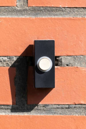 A close up straight portrait of a black and white old plastic doorbell on a red brick wall. The device is ready to be used for someone to announce that they have arived by pressing it and ringing it. 写真素材