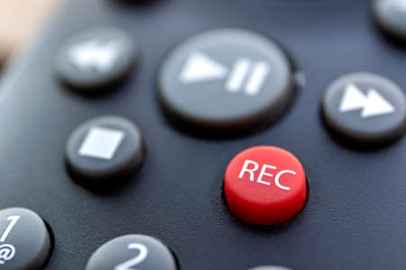 A close up portrait of the record button of a television or other multimedia device to start recording sound or a series or movie. it is surrounded by the buttons needed to play it again.