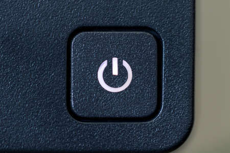A close up portrait of an on or off button of a PC screen. The computor monitor is turned on because the light in the symbol of the button is on.