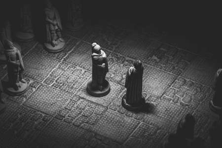 A black and white portrait of two soldier pieces of a game of chess facing each other in the beginning of the strategic duel. The chessboard and the pieces are made of stone.