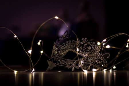 A portrait of a mask lying on a table surrounded by lights. The dark environment casts some mystery over the mask.
