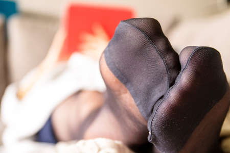 A close up of the black nylon feet of a woman dressed in pantyhose or stockings with reinforced toes, lying on a couch in a living room relaxing and using her tablet computer in the background.