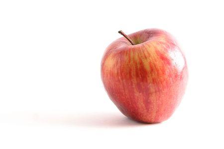 Red apple against white background, hi-key. Imagens